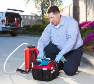 an exterminator is preparing his equipment
